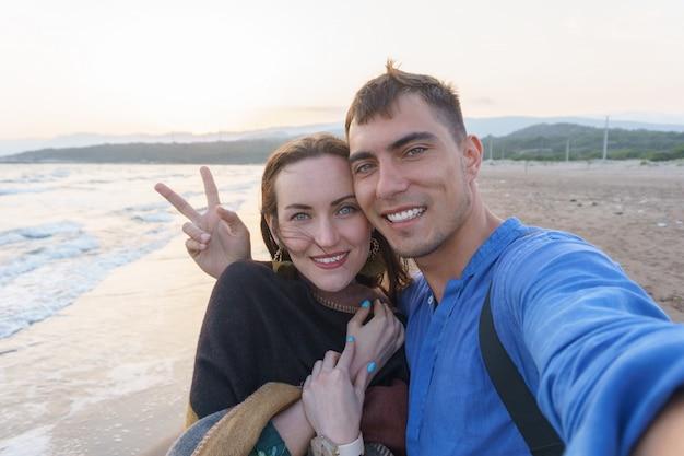 夕暮れ時のビーチで平和のシンボルと恋にselfieカップル
