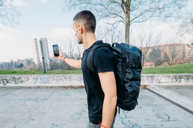 若い男がselfieを取ってスマートフォンを使用して屋外