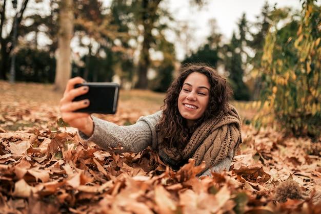 秋の公園でselfieを作る女の子。