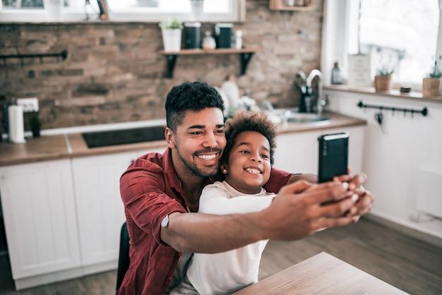 幸せなアフリカ系アメリカ人男性と彼の娘が台所のテーブルでselfieを取っています。