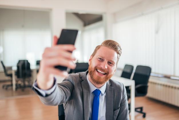 Счастливый бизнесмен принимая selfie на работе.