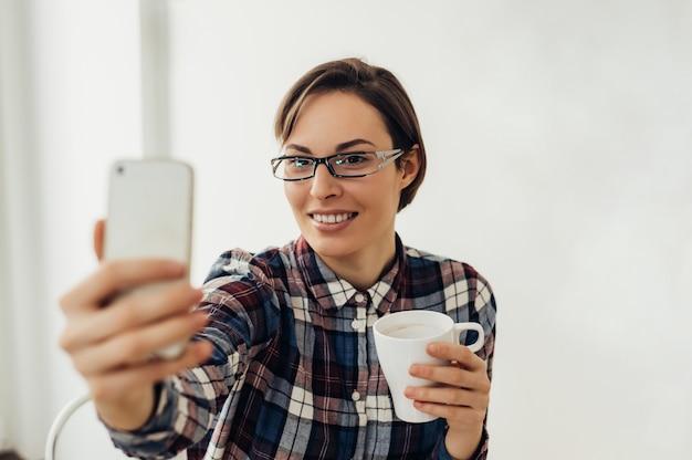 Selfieを取ってメガネで美しい少女