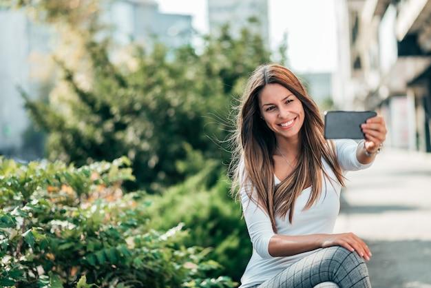 町の通りでselfieを作る笑顔の若い女性の肖像画。