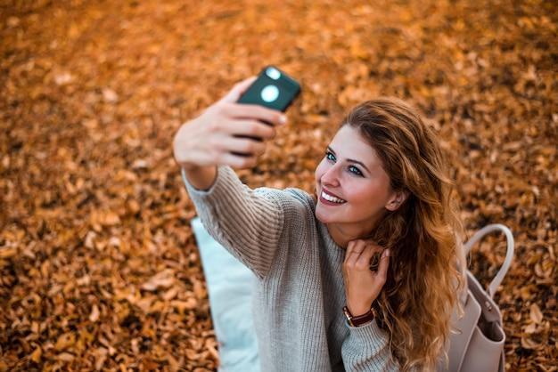 公園でselfieを取っているブロガーの女の子。ブログのための新しいコンテンツを作る。