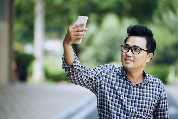 メガネとスマートフォンでselfieを取って格子縞のシャツの若いアジア人