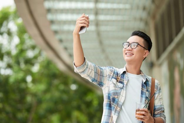 カジュアルな服装のアジア人男性飲料とモールを歩いて、スマートフォンでselfieを取る