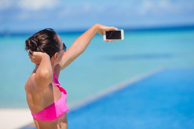 ビーチでの休暇中に屋外の電話でselfieを取っている若い美しい女性