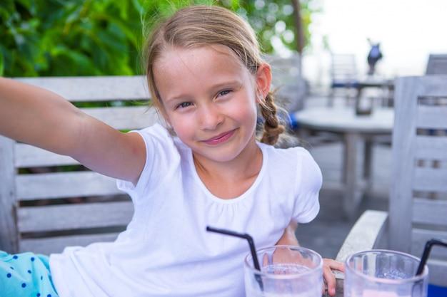 Selfieを取って、屋外カフェでおいしいカクテルを飲む女の子