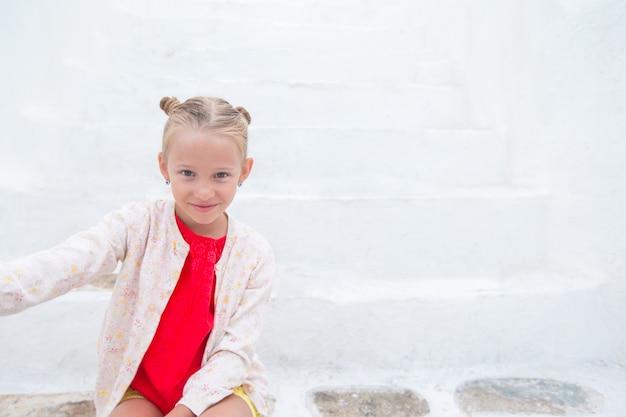 狭い通りにギリシャの村で屋外selfie写真を撮る愛らしい少女