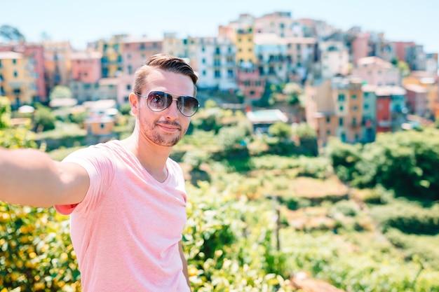 Selfieを取って若い観光客背景美しい古いイタリアの村、チンクエテッレ、リグーリア