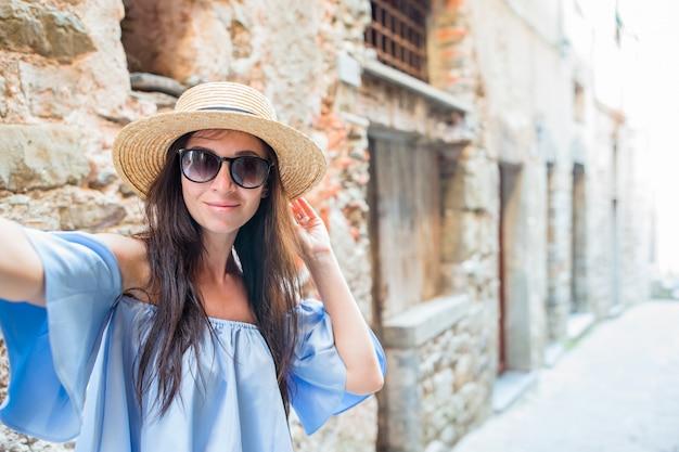 女性は都市で彼女のスマートフォンでselfieを取ります。自己写真を撮る若い魅力的な観光客