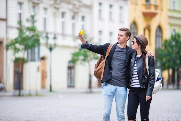 ヨーロッパ旅行の白人カップルによるselfie写真。ロマンチックな旅行の女性と愛の男の笑顔幸せなセルフポートレートを取る屋外の休暇中にプラハで旅行