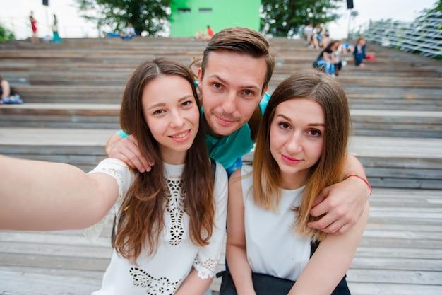 Группа в составе счастливые предназначенные для подростков друзья смеясь над и принимая selfie на улице. трое друзей смотрят фотографировать с планшетного пк в парке