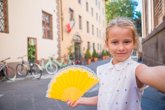 ヨーロッパの都市で屋外のselfieを取っている愛らしい幸せな女の子。白人の子供の肖像画は、旧市街で夏休みを楽しむ