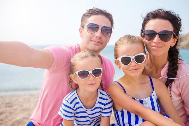 ビーチでselfieを取る若い美しい家族