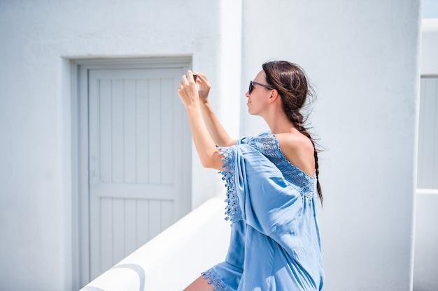 休暇中に屋外の携帯電話でselfieを取る若い美しい女性