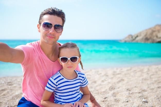 若い父親と小さな子供がビーチでselfie写真を撮る