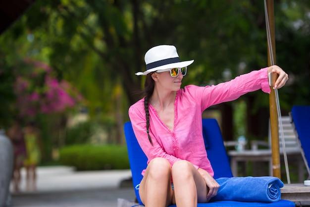 ビーチでの休暇中に屋外の携帯電話でselfieを取る若い美しい女性