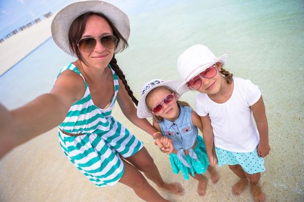 母と熱帯のビーチでselfieを取っている女の子