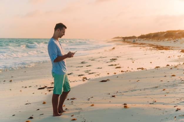 Молодой человек принимает selfie на фоне пляжа на море