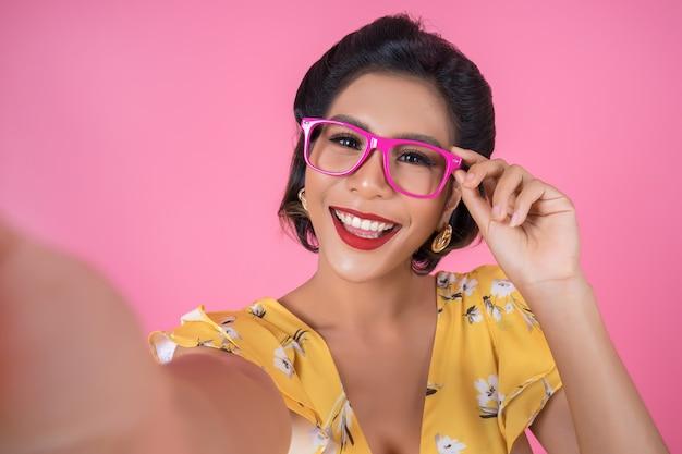 美しいファッションの女性は彼女の携帯電話で写真selfieを撮る
