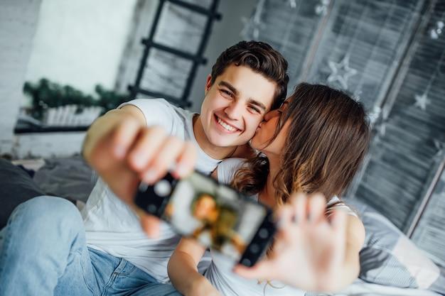 彼らの部屋で美しいカップルは、スマートフォンでselfieを作る
