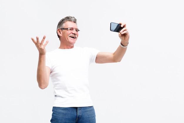 おじいちゃんがアクティブなライフスタイルをリードするスマートフォンでselfieを作る深刻な年配の男性。