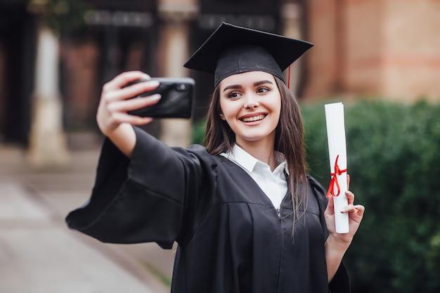 卒業帽子とガウンで卒業した女性は、屋外で共同selfieを作ります。