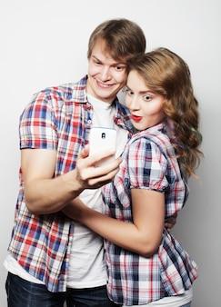 スマートフォン、selfieと楽しい笑顔のカップル。
