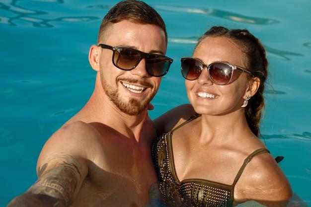 幸せなボーイフレンドとガールフレンドのスイミングプールで休んでいる間selfieを取る