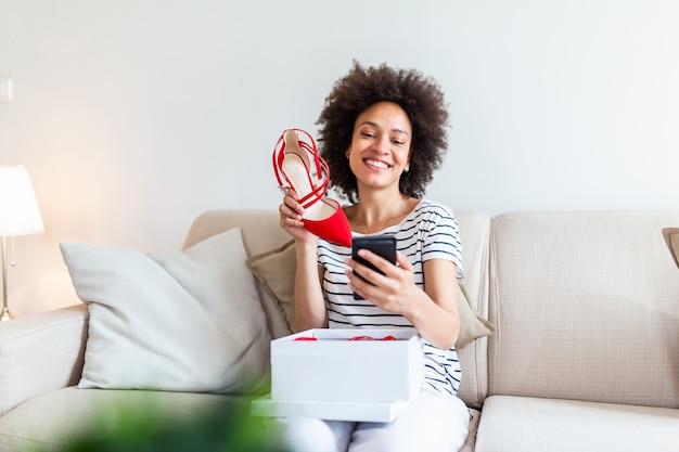 Улыбается женщина, распаковка почтовой посылки и принимая selfie с ее новыми покупками с помощью смартфона.