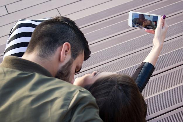 Захват ярких моментов. радостный молодой любви пара, делая selfie на камеру, стоя на открытом воздухе.
