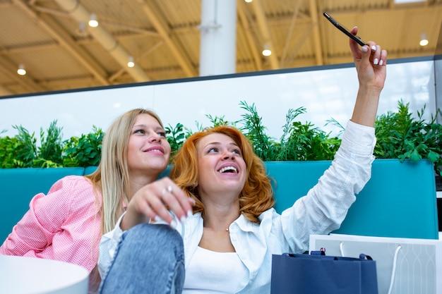 幸せな友人は、ショッピングモールで買い物しながらselfieを取っています。