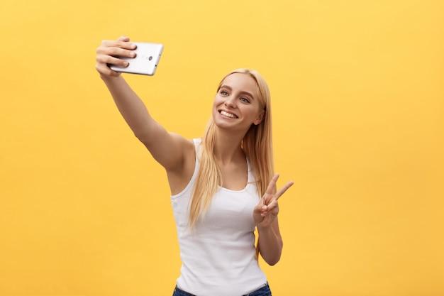 黄色の背景に分離されたselfieを取って白いシャツで陽気な笑顔の女性の肖像画