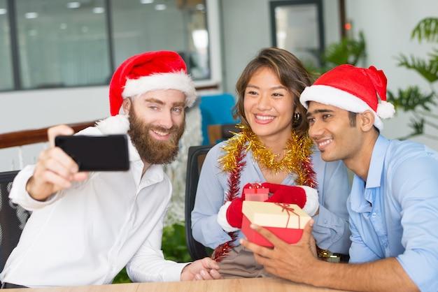 陽気な事業チームのクリスマスselfieを引き継ぐ