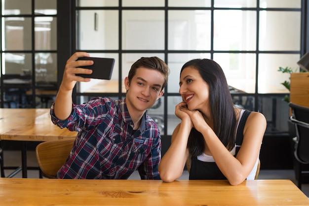 彼のガールフレンドとselfieを取って幸せな男の肖像