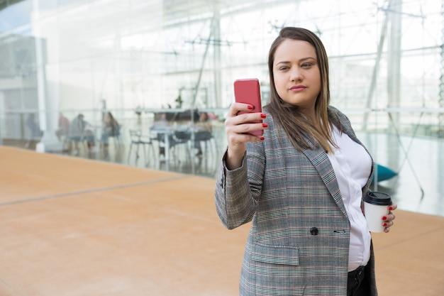 屋外の電話でselfie写真を撮る深刻なビジネス女性