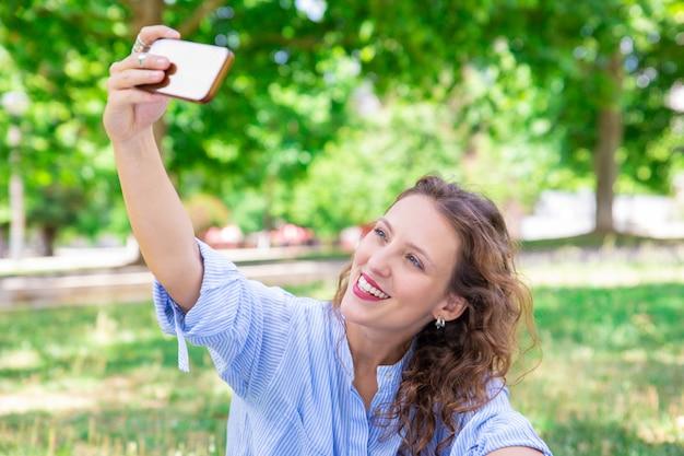 陽気な若い女性がスマートフォンでselfieのポーズ