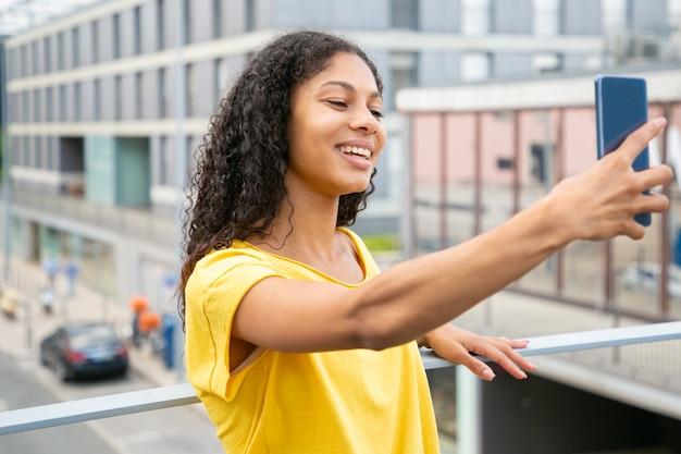 Счастливая радостная латинская девушка принимая selfie снаружи