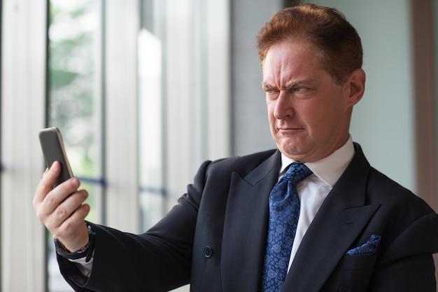 Хмурый бизнесмен, принимая selfie на мобильный телефон