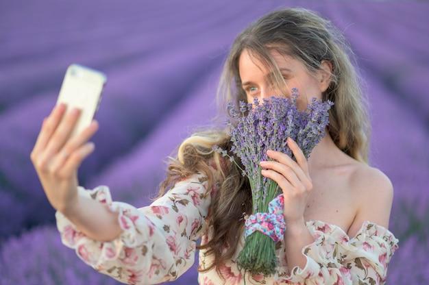 Selfieを取って日没でラベンダー畑の女性