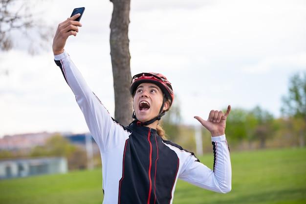 スポーツウェアとヘルメットのシャカの手サインを示し、公園でスマートフォンでselfieを取る若い陽気な男性サイクリスト