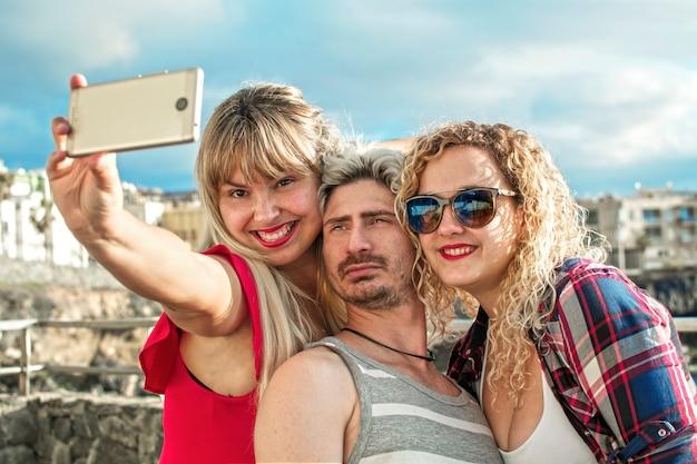 屋外で彼らのスマートフォンでselfieを取って幸せと金髪の若者