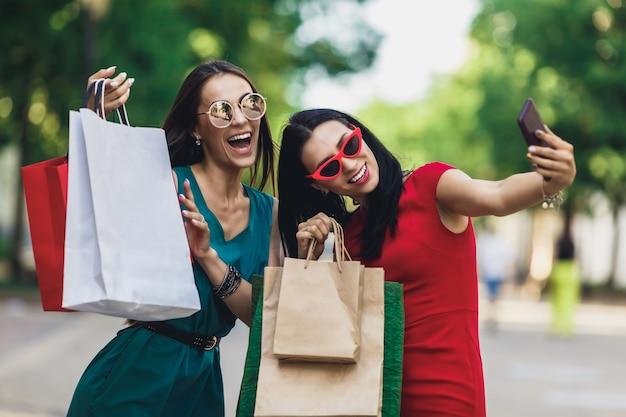 サングラスで買い物袋を保持している、スマートフォンでselfieを作ると笑顔で美しい幸せな女の子。