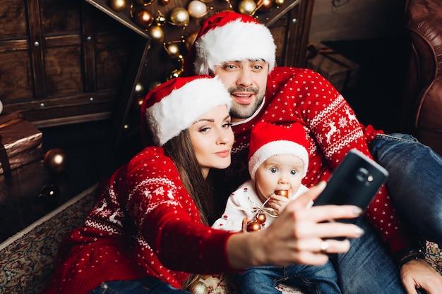 携帯電話でselfieを取って両親とかわいい赤ちゃん