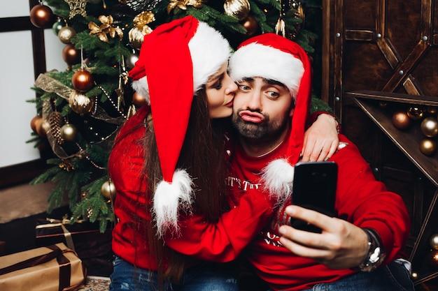 携帯電話でselfieを作るサンタ帽子で素敵なカップル