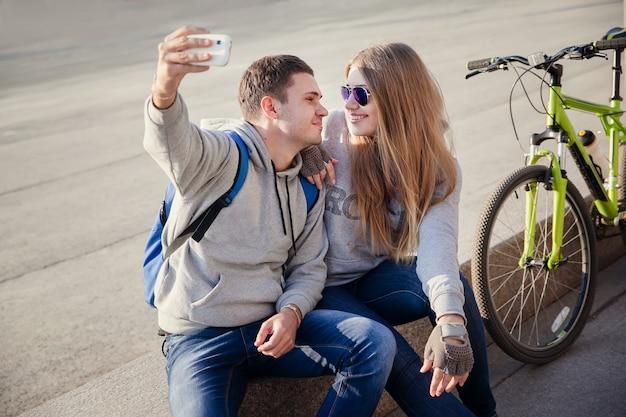 市内のselfieのスマートフォンを使用して若いカップル