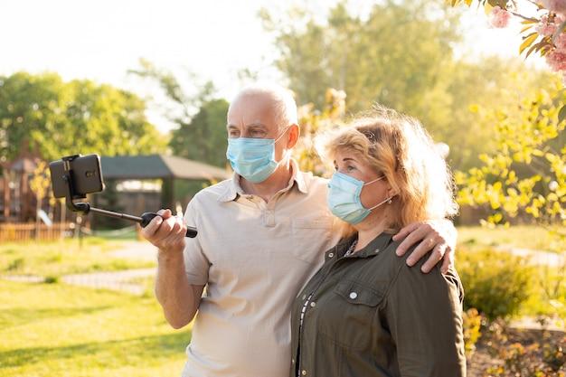 中高年カップルselfieを作るとコロナウイルスから保護するために医療マスクを着て春または夏の公園で抱きしめる
