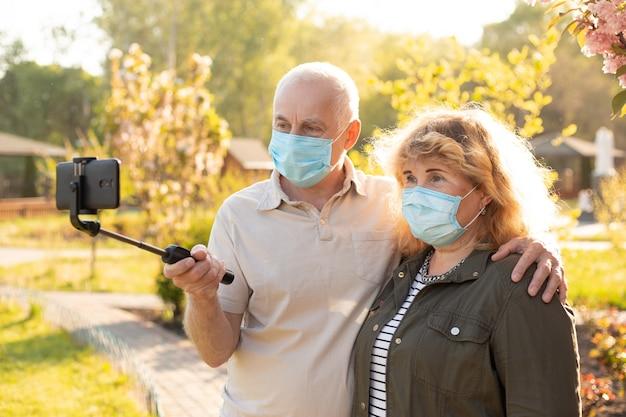 コロナウイルスから保護するために医療マスクを身に着けている春または夏の公園でselfieを作り、抱きしめる高齢者のカップル