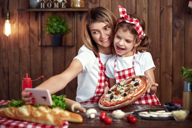 母と娘のスマートフォンでピザとselfieを取る